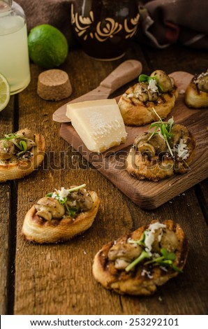 Mushroom snacks on grilled baguette, topped with parmesan cheese and microgreens, fresh lime juice
