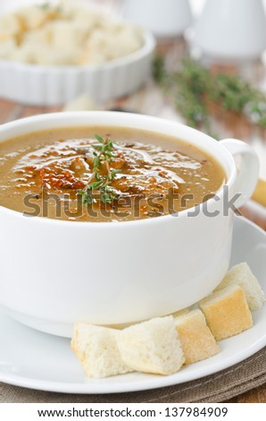 Mushroom soup in a white bowl with croutons and thyme close-up selective focus - stock photo
