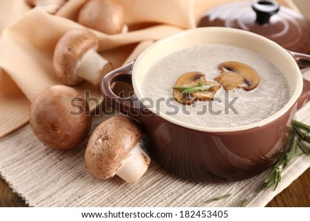 Mushroom soup in pot, on wooden background - stock photo