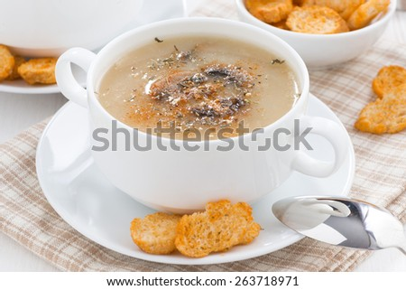 mushroom soup puree with croutons in white bowl, close-up - stock photo