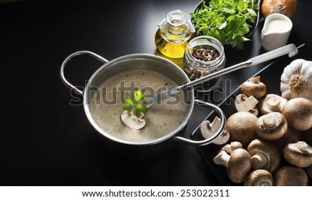 Mushroom soup with ingredients on the table - stock photo