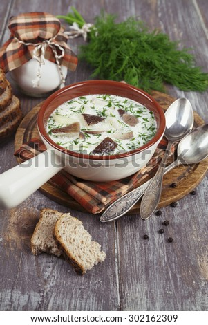 Mushroom soup with sour cream  in the bowl on the table