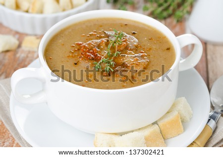 mushroom soup with thyme and croutons in the bowl, horizontal close-up
