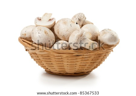 mushrooms champignon in a wicker basket isolated on white background - stock photo