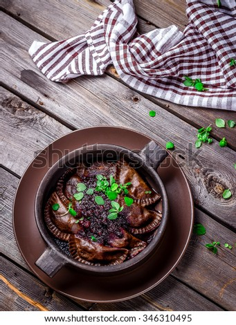 Mushrooms dumplings in a bowl on wooden table. Style rustic, selective focus.  - stock photo
