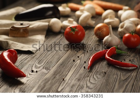 Mushrooms, eggplant, tomatoes, pepper, carrot, onion, garlic on an old brushed wooden table - stock photo