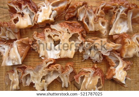 Mushrooms Gyromitra lying on a wooden table and sliced for further processing. Background with mushrooms. Top view.