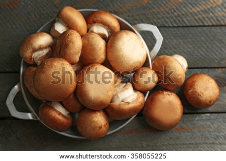 Mushrooms in bowl on wooden surface - stock photo