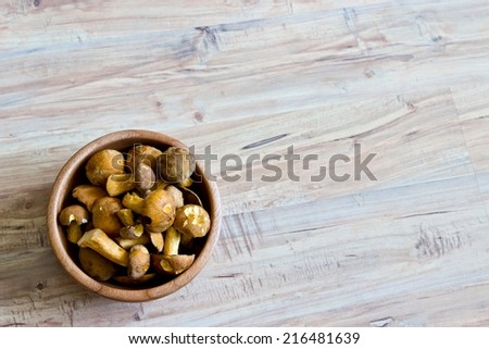 Mushrooms in wooden bowl. Object at the left part of image - stock photo