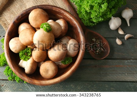 Mushrooms in wooden bowl on wooden surface - stock photo