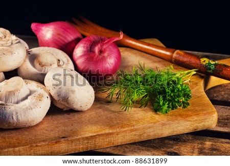 Mushrooms, onions and fresh herbs on a cutting board (focus on the mushrooms) - stock photo