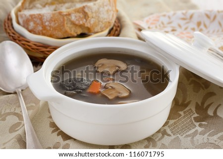 mushrooms soup in the bowl with spoon and bread