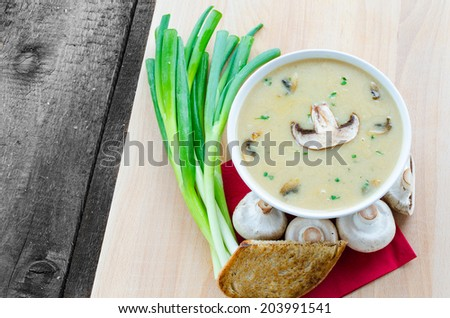 Mushrooms soup with spring onion and baked toast bread - stock photo