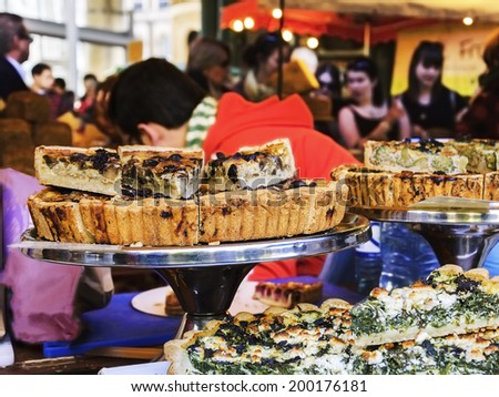 Mushrooms, spinach and broccoli pies on display at pastry stall in colorful food market - a famous Borough Market (London, England). People buying food at backgrounds. Selective focus. - stock photo