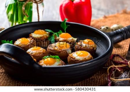 Mushrooms with quail eggs. Mushrooms on black pan. Quail eggs, pepper ...