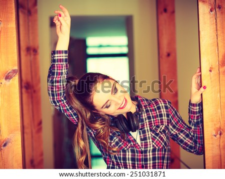 Music and technology concept - smiling teenage girl wearing plaid shirt with headphones listening mp3 dancing at home - stock photo