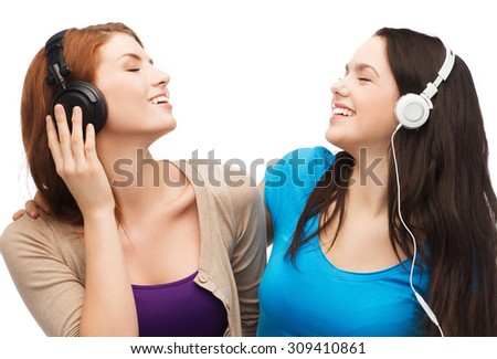music and technology concept - two smiling teenagers with closed eyes listeting to music with headphones - stock photo