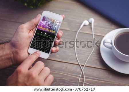 Music app against person holding smart phone at desk - stock photo