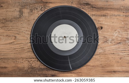 Music background of black gramophone Vinyl record on old retro vintage aged wooden table in the closeup Empty space for inscription  - stock photo