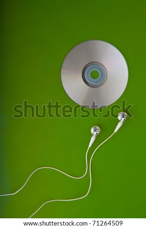 music CD with earphones headphones or earbuds on green background listening  songs on mp3 player white and silver phones for a portable radio - stock photo