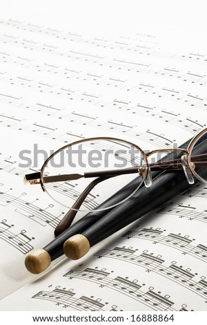 music charts ,with drums stick and glasses on top