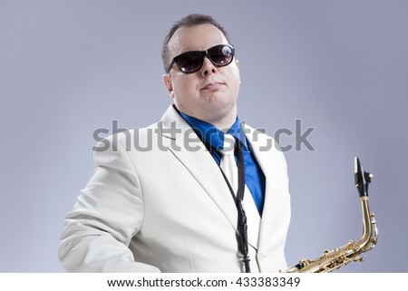 Music Concept and Ideas. Handsome Caucasian Musician with Alto Saxophone Posing in White Suit Against Gray. Horizontal Image - stock photo