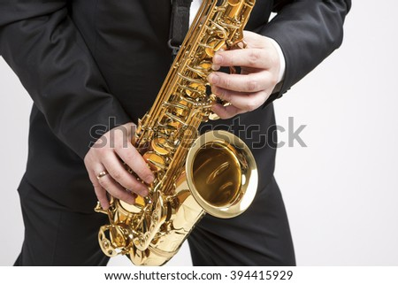 Music Concept. Closeup of Hands of Saxophone Player Playing on Saxophone Against White.Horizontal Image - stock photo