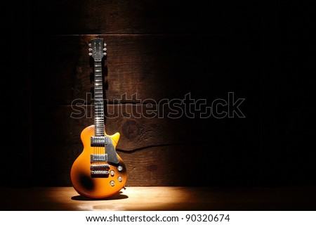 Music concept.Electric guitar standing near wooden wall under beam of light - stock photo