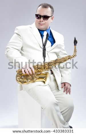 Music Concept. Portrait of Handsome Caucasian Musician With Alto Saxophone Posing In White Suit Against White Background. Wearing Black Sunglasses.Vertical Image Composition - stock photo