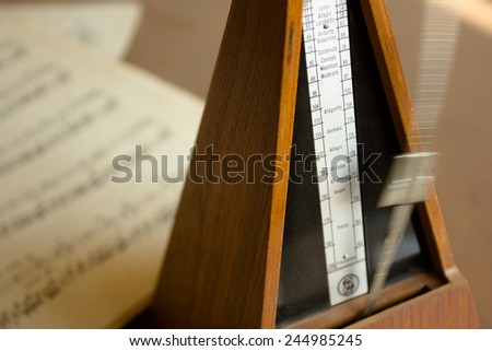 Music concept: vintage wooden metronome sets the rhythm by swinging pendulum, staying on the note sheets - stock photo