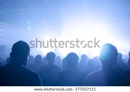 Music concert crowds illuminated from stage lights (very shallow depth of field) - stock photo