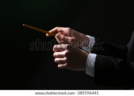 Music conductor directing with baton on black background, close up - stock photo