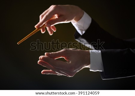 Music conductor directing with baton on black lightened background, close up