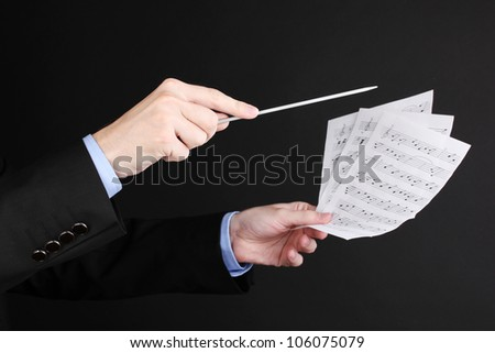 Music conductor hands with baton and notes isolated on black - stock photo