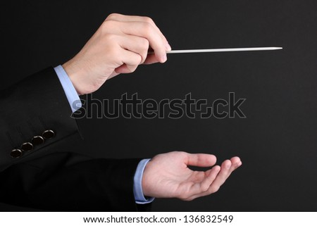 Music conductor hands with baton isolated on black - stock photo