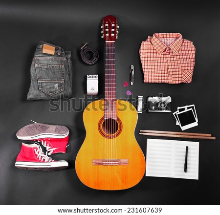 Music equipment, clothes and footwear on black background - stock photo