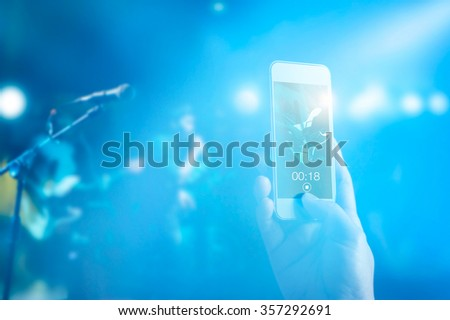 Music fans takes a photo guitarist on stage in concert on smart phone, Pastel color tone and soft focus - stock photo