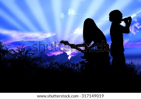 Music for the Earth Rocker and Guitarist are Singing and Playing Rock Music Against the Background of Sunrise Blue Sky - stock photo