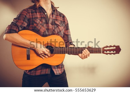 Music hobby people concept. Male hands with guitar. Musician playing the wooden instrument.