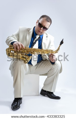 Music Ideas and Concepts. Handsome and Expressive Caucasian Musician With Alto Saxophone Posing In Sunglasses Against White Background. Vertical Shot - stock photo