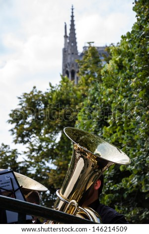 Music in Paris. Golden tubes, part of male body, green trees and Notre Dame de Paris Cathedral at backgrounds. - stock photo