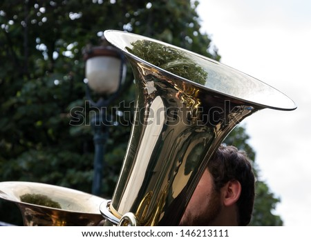 Music in park - golden tubes, part of male head, streetlight and green trees. - stock photo