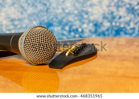 Music instruments concept the Microphone acoustic guitar and blue abstract bokeh background.