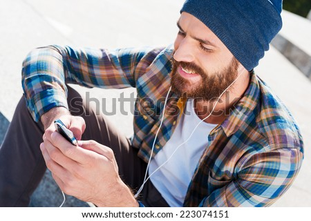 Music is my life! Handsome young bearded man smiling while listening to music - stock photo