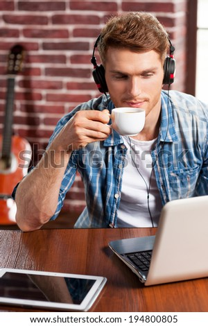 Music is my life. Top view of handsome young man in headphones working on laptop and drinking coffee while acoustic guitar laying in the background  - stock photo