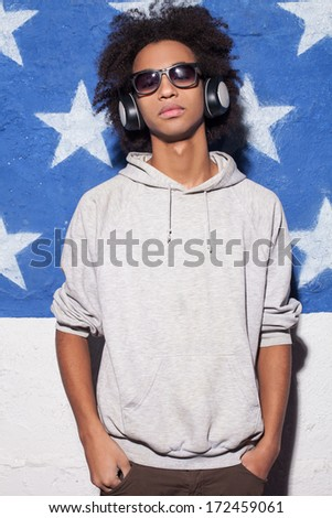 Music lover. Confident young African man in headphones standing against American flag and listening to the music - stock photo