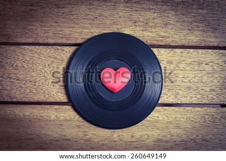 Music Lover - Vinyl with red love heart on a wooden surface - stock photo