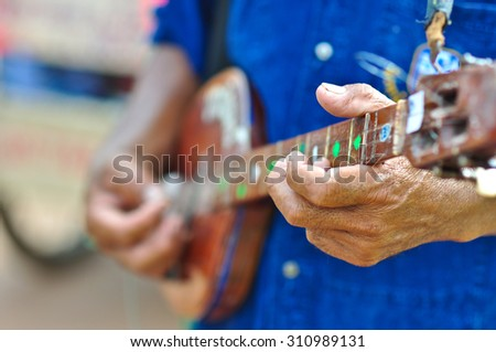 music man is playing steel string indian lute in festival thailand before raining season the body of this little guitar made from wood - stock photo