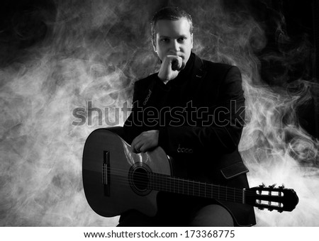 Music. Musician in black suit with a guitar - stock photo