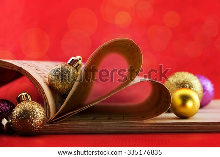 Music notation book with pages shaping heart and Christmas ornaments with bokeh lights - stock photo
